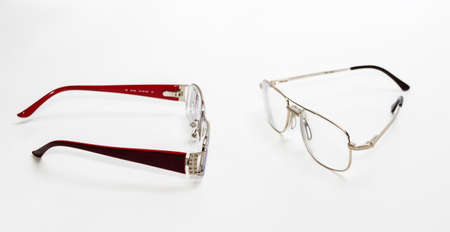 rectification: elegance womens glasses and mens glasses in thin rim located opposite on a light background Stock Photo