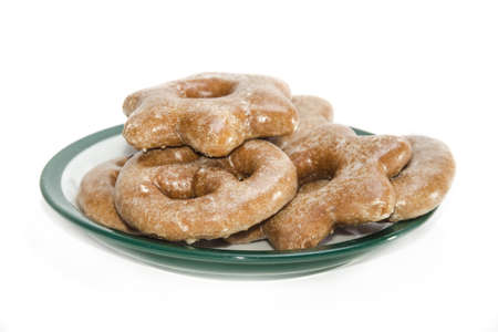 icing sugar: gingerbread of different shapes coated with icing sugar on a platter on light background