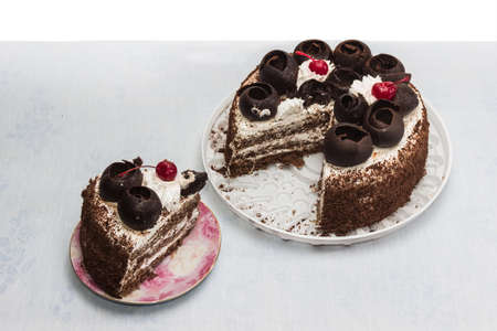 Layer-cake decorated with chocolate, whipped cream and cherries and cut out a piece of cake on a platter on the bright tablecloth. Imagens