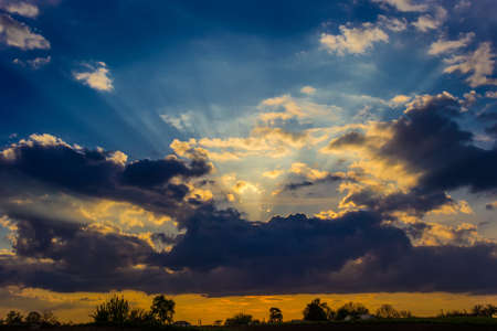 Sky with clouds, through which the suns rays make their way during sunset. Rural landscape photo