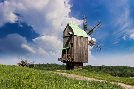 ethnographical: Old windmill on a background of forest and sky. Ukrainian Museum of Folk Architecture and Life, Kiev, Ukraine. Editorial