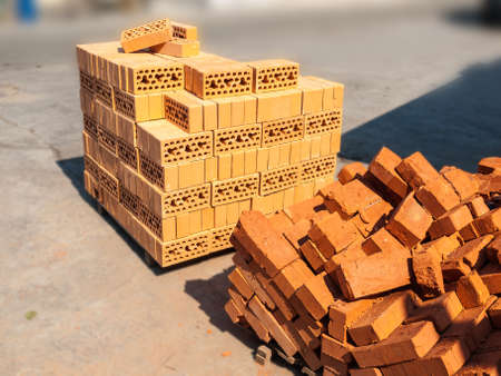 varying: Two pallets with red brick of varying quality in stock. Stock Photo