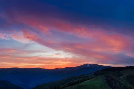 Sky with red, crimson clouds after sunset over the ridge. Carpathians.