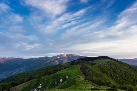 forested: Landscape with mountain ranges, forested slopes, mountain pasture with buildings summer farm, snowfields on top of the ridge and sky during sunrise. Carpathians. Stock Photo