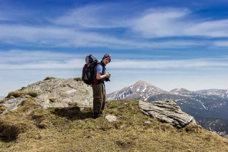 Young tourist with a backpack on the background of a mountain range with snowfields and sky. Carpathians. Stock Photo