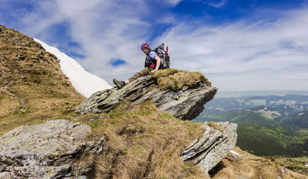 ledge: Young tourist with a backpack on a rocky ledge of the mountain ridge on a background of forested mountains, snowfields and sky. Carpathians.