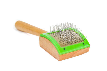 prongs: Wooden comb for cats with curved metal prongs with drops on the ends on a light background. Isolation.
