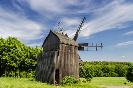 ethnographical: Old windmill on a background of forest and sky with blurred clouds. Ukrainian Museum of Folk Architecture and Life, Kiev, Ukraine.