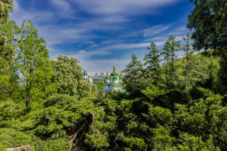 sanctity: View of the Vydubychi monastery through the lush vegetation of the park on a background of flowering chestnut trees and the sky with blurred clouds.  Kyiv, Ukraine.