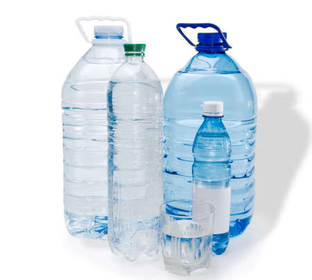 safe drinking water: Several different sizes of plastic bottles and glassful with drinking water on a light background. Isolation. Stock Photo