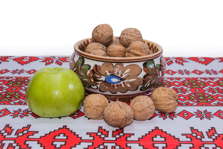 Bowl with nuts, green apple and walnuts on the tablecloth with a national ornament with a white background.