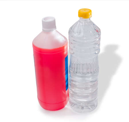 cooling system: Plastic bottle with antifreeze and bottle with distilled water to prepare a coolant for automotive engine cooling system. Isolation. Stock Photo