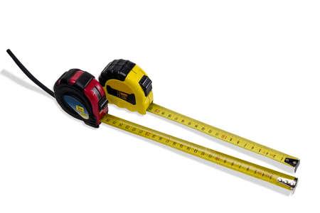 cintas metricas: Dos cinta m�trica en una caja roja y amarilla para la medici�n en el sistema m�trico con parcialmente retirado la cinta amarilla sobre fondo claro. Aislamiento. Foto de archivo