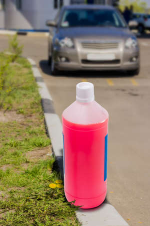 cooling system: Plastic bottle with antifreeze for automotive engine cooling system on background blurred car on the back plane.