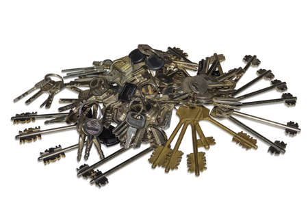 brassy: Many bunch of different keys to door locks on a light background. Isolation.