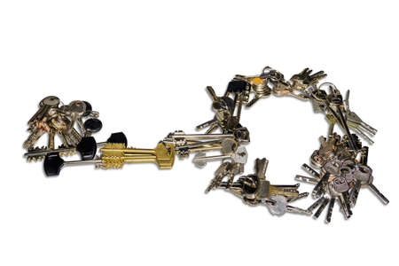 safeness: Many bunch of different keys to door locks, laid out in the form of a single large key on a light background. Isolation.
