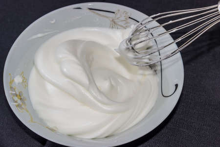 Whipped egg whites in a bowl and whisk from the mixer on a dark background
