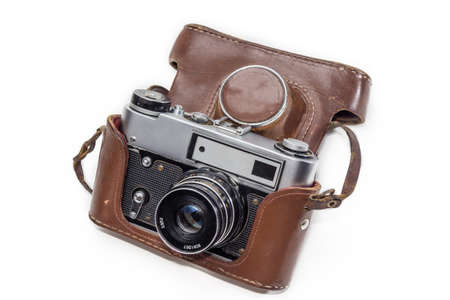 recollection: The old film camera in a brown leather case on a light background. Isolation.