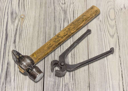 Old hammer and pliers for pulling out nails on the surface from an old blackened wooden planks.