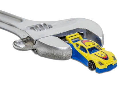 fix jaw: Small plastic toy car between the jaws adjustable wrench on a light . Isolation. Stock Photo