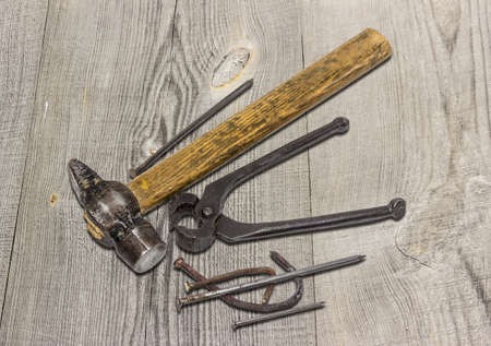 Old hammer pliers for pulling out nails and several different nails on the surface from an old blackened wooden planks.