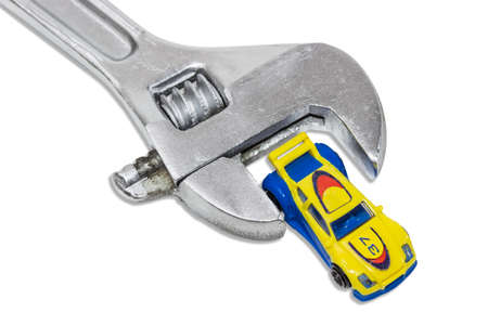 strengthen hand: Small plastic toy car between the jaws adjustable wrench on a light background. Isolation. Stock Photo