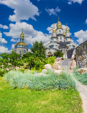Orthodox church with a separate bell tower with a lawn and ornamental shrubs in the foreground against the sky with clouds Stock fotó