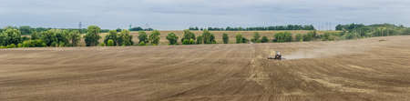 plowed field: Panorama plowed field with tractors in agricultural work on the background of trees