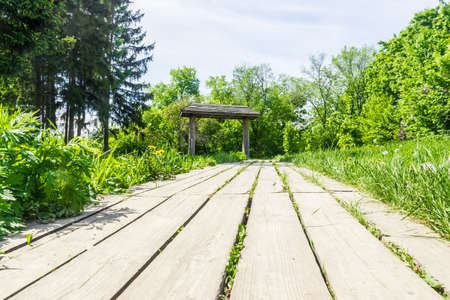 flower garden path: Garden path, lined with wooden planks in the grass, leading to a decorative wooden gate with a roof. Stock Photo