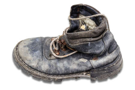 loops: Old ragged dirty black leather boot with rusty hooks and loops for shoelaces on a light background Stock Photo