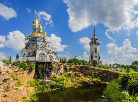 Orthodox church with a separate bell tower with a pond in the foreground against the sky with clouds Stock fotó