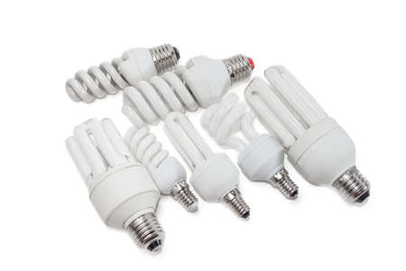 frugal: Several energysaving fluorescent electric lamps different sizes with flasks of different shapes on a light background. Isolation.