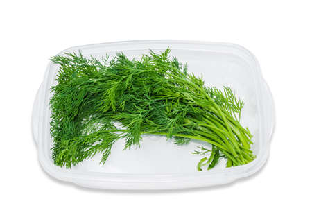 greenness: Transparent plastic tray with fresh dill on a light background. Isolation.