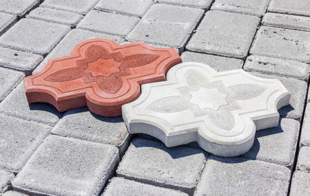 paver: One red and one white concrete curly interlocking pavers with ornament on the surface of another gray paver on depot