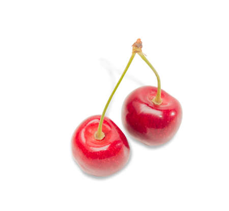 isolation: Two ripe dark red cherries on a light background. Isolation.