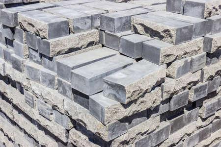 거친 자연석의 형태로 만들어진 약간의 측면이있는 회색 장식 벽돌로 된 팔레트