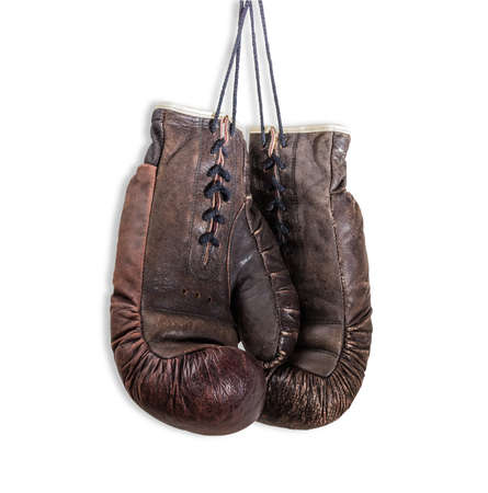 Old worn leather brown boxing gloves, that hang on a laces. Isolation on a light background. Stock Photo