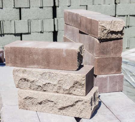 거친 자연석의 형태로 만들어진 몇 가지 측면 얼굴을 가진 갈색 장식 벽돌
