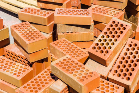red brick: Red perforated bricks with round holes in warehouse closeup. Stock Photo