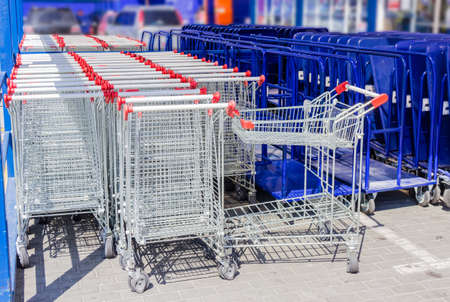 shopping carriage: Rows of ordinary shopping baskets and trolleys for heavy building materials in the parking lot near the supermarket building Stock Photo