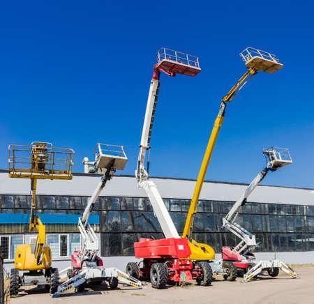 Plusieurs différentes plates-formes de travail aérien mobiles - automoteur ascenseur hydraulique de flèche articulée contre le ciel et bâtiment industriel Banque d'images - 42896494
