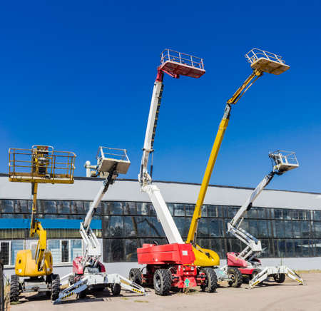 Several various mobile aerial work platform - self propelled hydraulic articulated boom lift against the sky and industrial building