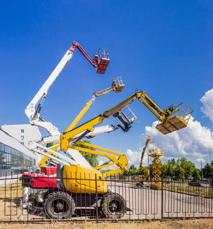 Several various mobile aerial work platform - self propelled hydraulic articulated boom lift and scissor lift against the sky, trees and industrial building Standard-Bild