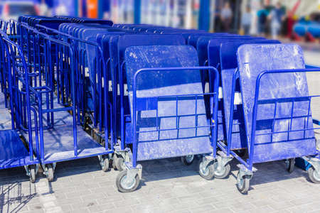 building materials: Rows of blue trolleys for heavy building materials in the parking lot near the supermarket building