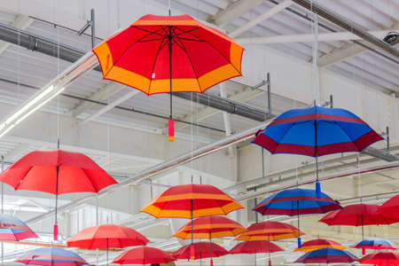 collapsible: Multicolored collapsible umbrellas - red, blue, orange, suspended near the ceiling of the office building