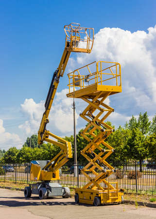 Two types of mobile aerial work platform - yellow scissor hydraulic lift and yellow hydraulic articulated boom lift against the sky with clouds and trees 스톡 콘텐츠