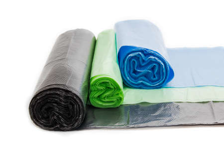 degradable: Garbage bags in rolls of different sizes and colors not harmful to the environment on a light background. Isolation.
