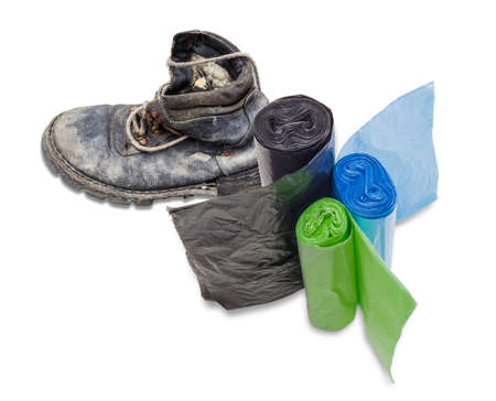 harmful: Three rolls of black, green and blue garbage bags of different sizes not harmful to the environment against the backdrop of an old ragged shoes. Isolation.
