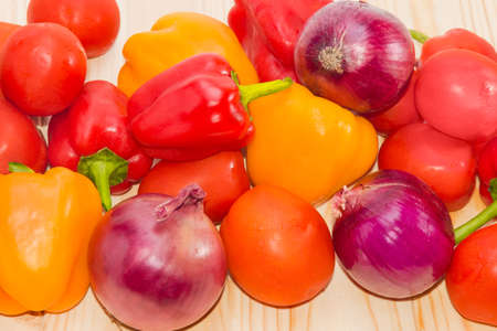 Fresh red and yellow bell peppers, tomatoes and red onions with dew drops closeup on wooden surface.