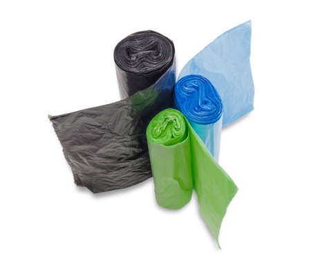 degradable: Three rolls of black, green and blue garbage bags of different sizes not harmful to the environment on a light background. Isolation.